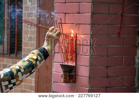 An Old Woman Offers A Sacrifice To The Heavenly Official.  Burning Incenses In Front Of The Sacrific