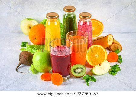 Green, Yellow, Purple Smoothies In Currant Bottles, Parsley, Apple, Kiwi, Orange On A Gray Table. Or