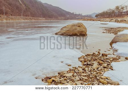 Landscape Of Frozen River With Rocky Shoreline And Large Boulder In Foreground On A Cold Overcast Wi