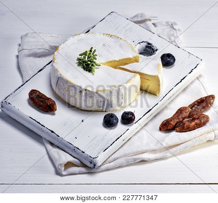 Round Camembert Cheese And Pieces Of Smoked Sausage On A White Wooden Board, White Wooden Table, Top