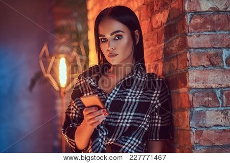 Close-up Portrait Of An Attractive Brunette Dressed In Flannel Shirt Holding A Phone Leaning On The