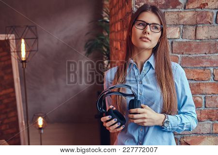 Portrait Of An Attractive Charming Brunette In Glasses And Blue Shirt Holds Headphones Leaning Again