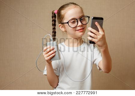 Cute Little Girl With Glasses Using Modern Smartphone And Portable Power Banks