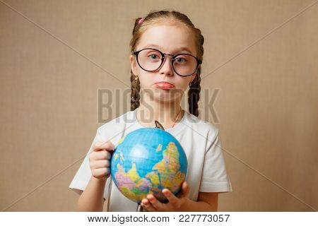 Pretty Child Girl With Glasses At Home Dreaming Of Travel And Tourism, Exploring The World Map And G