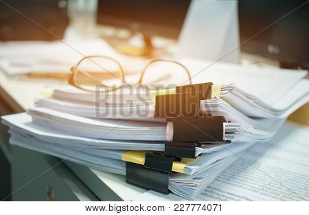 Glasses Placed On Unfinished Documents Stacks Of Paper Files On Computer Desk For Report , Piles Of