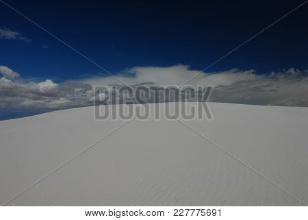 A View Looking Up A Large White Sand, Sand Dune, Into The Dark Blue Sky With White Puffy Clouds.