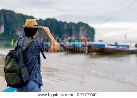 Young Man Traveler With Green Backpack And Hat Looking At The Sea With Long Boat Thailand Background