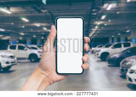 Man's Hand Shows Mobile Smartphone With White Screen In Vertical Position, Blurred Or Defocus Image