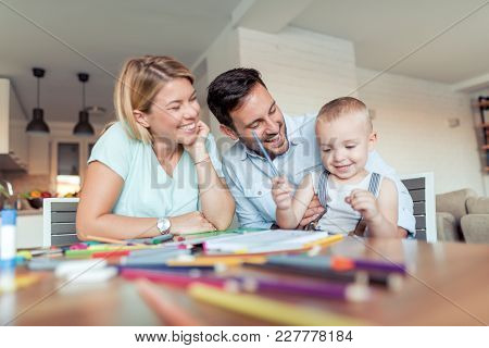 Father And Mother Teach His Son To Draw.