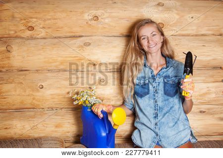 Woman with a shovel, a rake and a flower in a pot. Female gardener. Gardening
