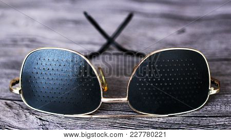 Black Medical Glasses With Holes On Wooden Background