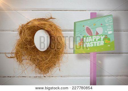 Easter egg hunt sign against white egg in nest on wooden table