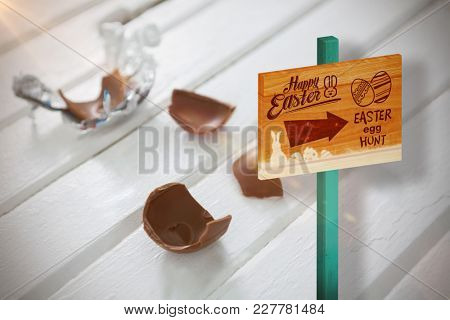 Easter egg hunt sign against broken chocolate easter on wooden surface