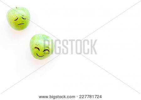 Basic Emotions Concept. Happy Smile And Sad Grimace Drawn On Apple. White Background Top View.