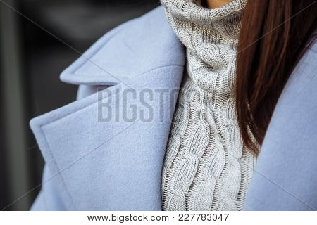Closeup Detail Of Women's Clothing. The Girl In A Warm Sweater And Coat.
