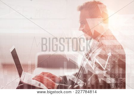 Stocks and shares against smiling businessman using laptop