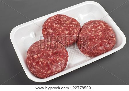 Tray With Raw Beef Burgers Isolated On Gray Background.
