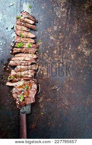 Traditional barbecue skirt steak sliced as close-up on a knife with copy space right