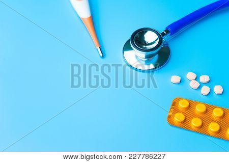 Doctor Office Desk With Medical Blister Of Capsule Pills Red Injection Syringe And Stethoscope.