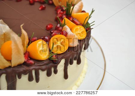Piece Of Cake With Chocolate Icing And Citrus Decoration. Tangerine Cake, With Pomegranate Seeds. Cl