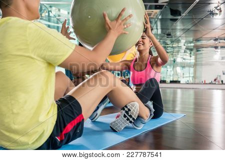 Cheerful young woman giving the fitness ball to her workout partner while doing crunches together for abdominal muscles in a modern health club