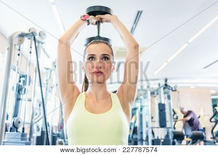 Portrait of a beautiful fit woman with can do attitude exercising triceps extension with dumbbell during workout in a modern fitness club