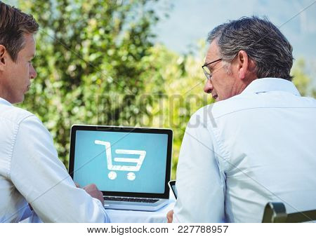 Digital composite of Two men using Laptop with Shopping trolley icon
