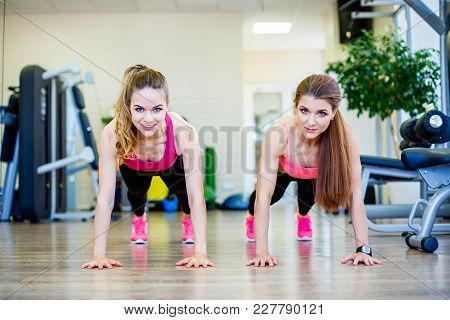 Two Sporty Girls Doing Push Ups At Gym