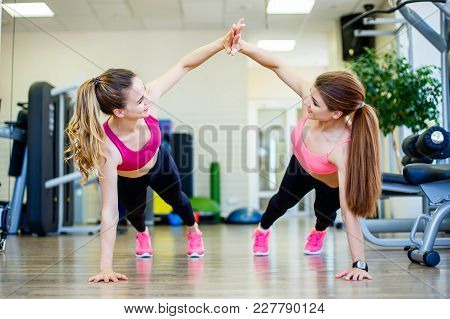 Two Female Friends Wearing Sportswear Giving High Five While Training On Floor In Gym
