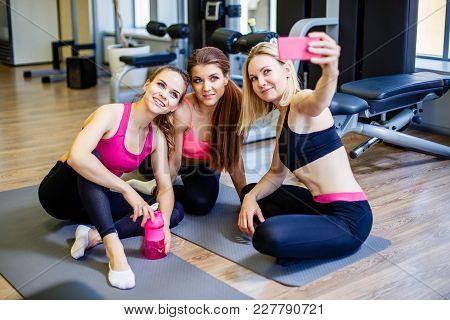 Happy Young Girls In Sportswear Taking Selfie In Gym. Three Female Friends In Healthclub Taking Self