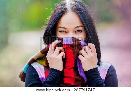 Brunet Girl With Colorful Scarf In The Park