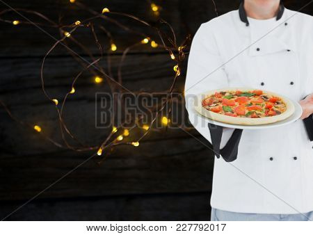 Digital composite of Chef with pizza. Wood and lights background