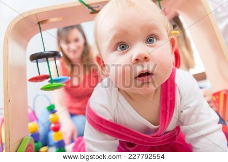 Close-up portrait of a cute baby girl with blue eyes and an intelligent facial expression, while playing on the floor with her mother at home