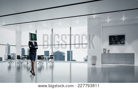 Business Woman In Suit With Monitor Instead Of Head Keeping Arms Crossed While Standing Inside Offic
