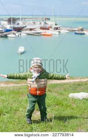Little Kid In Jacket And Hat Smiling And Spreading His Hands Imagining Flight On Background Of Sea B