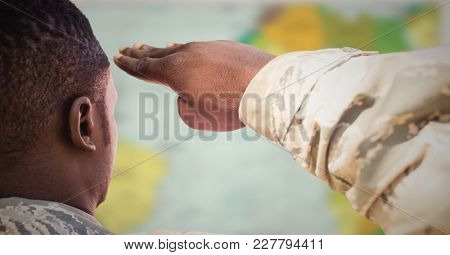 Digital composite of Back of soldier saluting against blurry map