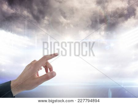 Digital composite of Hand pointing at cloudy sky over stadium lights