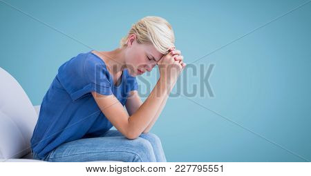 Digital composite of Woman sitting on couch with head on hands against blue background