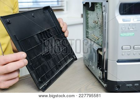 A Man Is Repairing The Musical System. He Is Removing The Lid.