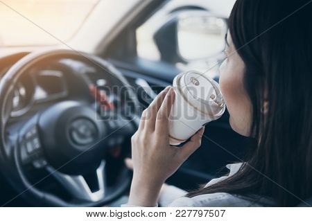 Asian Woman Holding Hot Coffee Cup Drinking While Driving