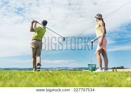 Full length of a young woman smiling while practicing the correct move for striking during golf class with a skilled professional player outdoors