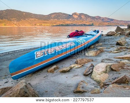 Fort Collins, CO, USA - September 3, 2017: Racing stand up paddleboard (All Star by Starboard) on a calm Horsetooth Reservoir at sunrise during Labor Day weekend.