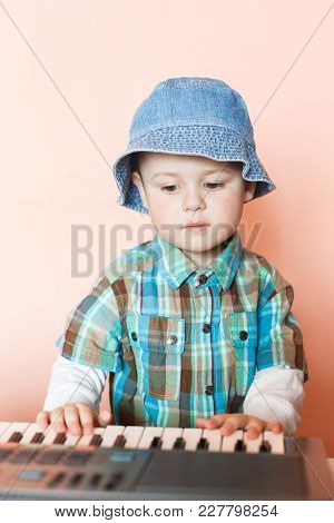 Little Cut Boy Playing The Digital Piano. Happy Childhood And Music. Musical Instrument Indoor.
