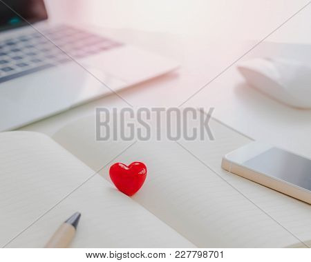 Valentines Day Theme,red Heart On Notebook With Pen,smartphone And Laptop On White Table In Office.c