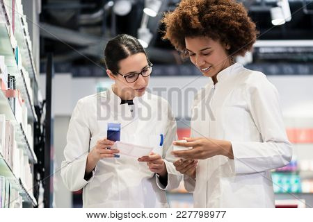 Low-angle view of two reliable pharmacists analyzing together a medical prescription and two different packages of medicine during work in a modern drugstore