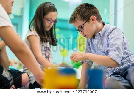 Cute girl wearing eyeglasses while playing with concentration a creative game next to her colleague in the classroom of a modern kindergarten