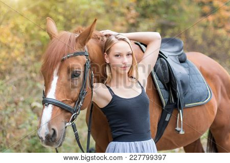 A Young, Blonde Girl Posing With A Horse, A Beautiful Girl And A Strong Horse. In The Forest