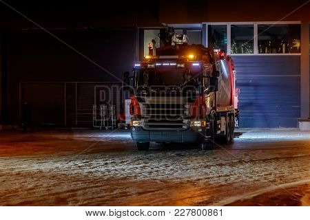 Garbage Collecting Truck Leaves Garage To Collect Garbage. Truck Moves On Snow Covered Road. Dark Ti