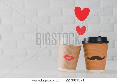 Two Coffee Cup With Smiling Face Of Man And Woman Together With Heart On White Brick Wall Background