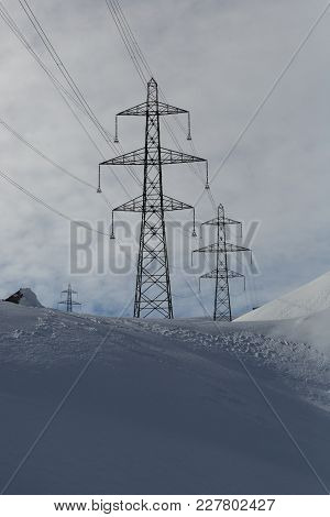 Electricity Pylons In Winter Mountains, White Snow
